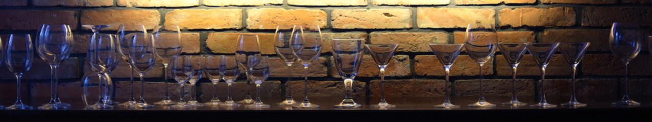 Fototapeta Glasses against the backdrop of an illuminated brick wall