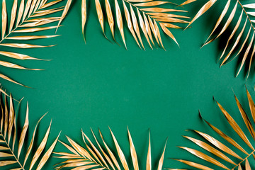 Wall Mural - Gold tropical palm leaves on green background. Flat lay, top view minimal concept.