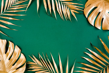 Photo on textile frame Palm tree Gold tropical palm leaves Monstera on green background. Flat lay, top view minimal concept.