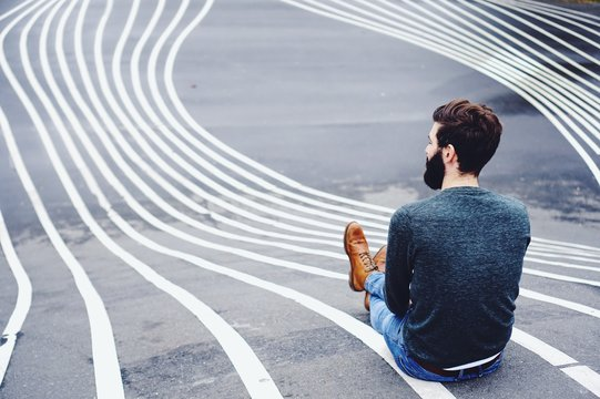 Rear View Of Man Sitting On Road Marking