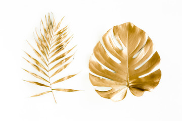 Wall Mural - Gold tropical palm leaves Monstera on white background. Flat lay, top view minimal concept.