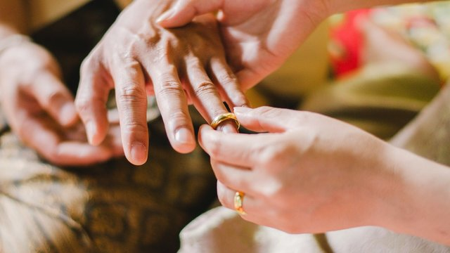 Cropped Image Of Bride Wearing Ring To Groom