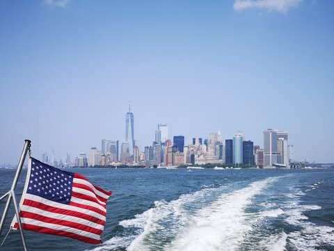 American Flag Waving Against Wake In Sea With Cityscape In Background