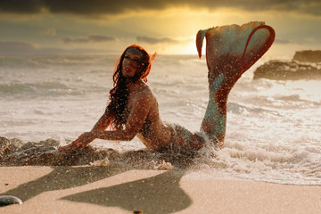 Caucasian redhead woman with mermaid tail arches her back in the surf at sunset