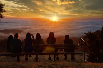 Group of figures watches sunset over clouds filling a forested valley