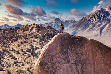 Man rock climbs on huge granite boulder in the Buttermilk area of Bishop, California with the Sierra Nevada  behind