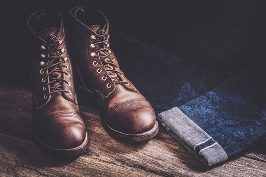Close-Up Of Leather Shoes With Jeans On Wooden Floor