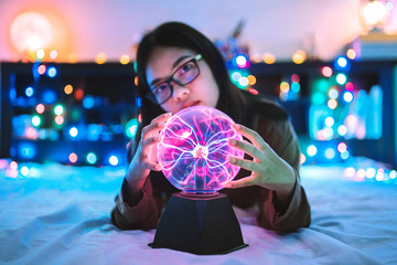 Portrait Of Woman Holding Plasma Ball On Bed