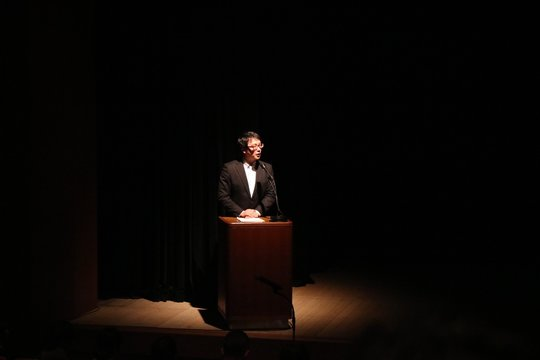 Mid Adult Man Looking Away While Giving Speech On Stage