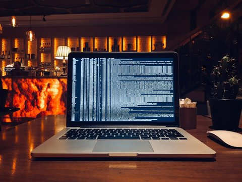 Computer Code On Laptop Screen At Table