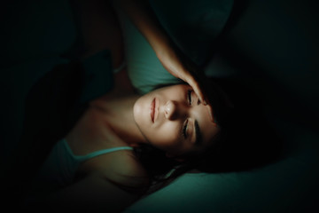 High Angle View Of Woman Using Phone While Lying On Bed In Darkroom