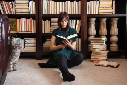 Young Woman Reading Book While Sitting Against Bookshelf In Library