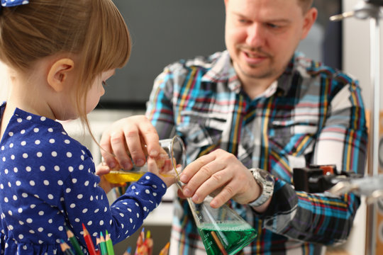 Man and little girl play with colourful liquids portrait. Young team clean research equipment colour reagent food additions flavor activity flavour concept