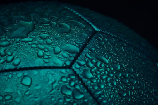 Close-Up Of Water Drops On Soccer Ball Against Black Background