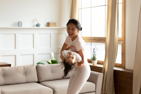 Overjoyed Vietnamese mom and small daughter have fun at home