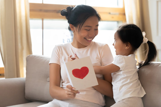 Little Asian girl greeting mom presenting postcard