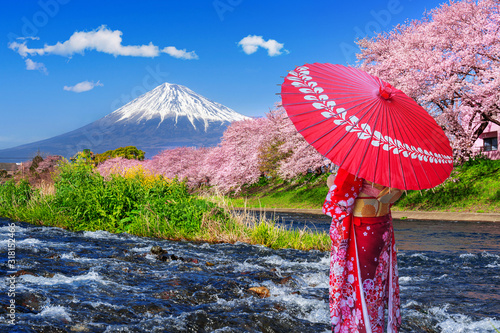 Wall mural Asian woman wearing japanese traditional kimono and looking at cherry blossoms with fuji mountains in Shizuoka, Japan.