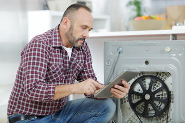 man looking at tablet by broekn down washing machine