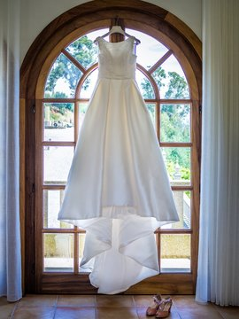 Simple wedding dress hanging from a big window with a garden under the sunlight on the background