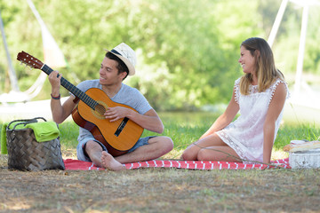 young couple having fun with guitar during picnic