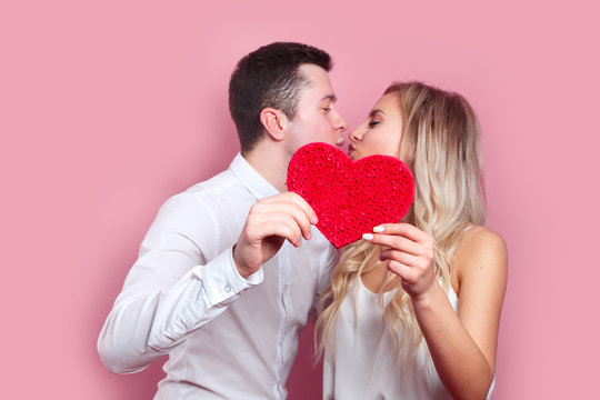 young couple kissing behind paper heart on pink background