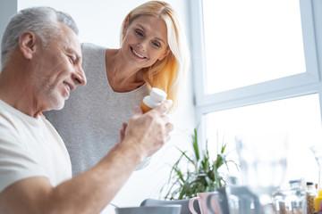 Happy woman and man looking at pills stock photo