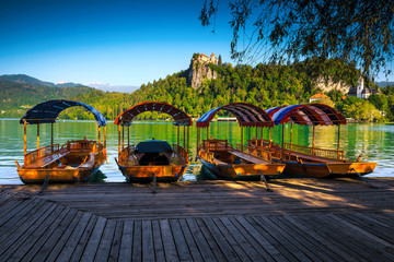 Wall Mural - Wooden Pletna boats anchored on the lake Bled, Slovenia