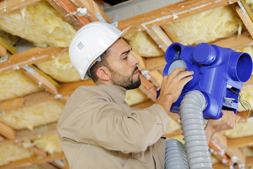 man working on ceiling pipes