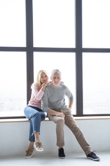 Couple sitting near the window and smiling stock photo