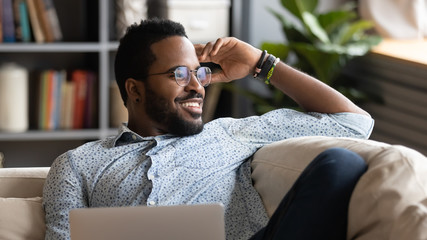 Happy african american man relaxing with laptop looking away dreaming