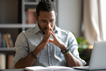 Young african american businessman praying sit at work desk