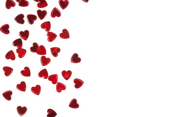 Red foil heart shaped confetti isolated on white backround.