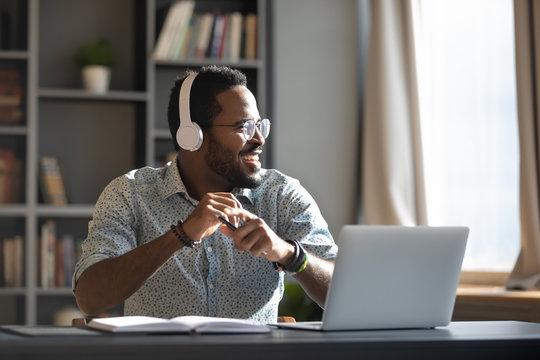 Happy millennial african businessman wear headphones listening music in office