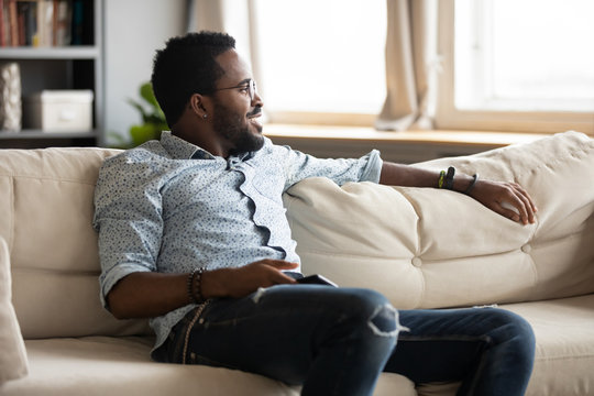 Relaxed african guy chill on sofa at home holding phone
