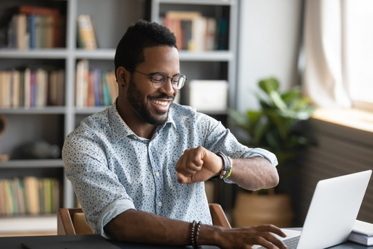 Happy african businessman worker looking at smart watch at work