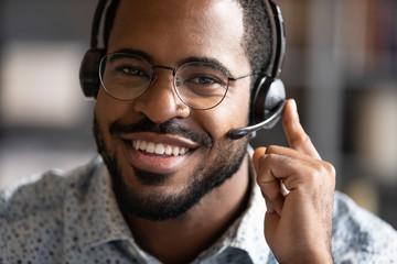 Happy friendly african telemarketing operator wear wireless headset portrait Fototapete