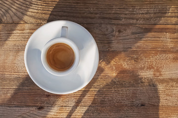 Fotobehang - Cup of coffee standing on the wooden e table in sunlight with dropping shadows