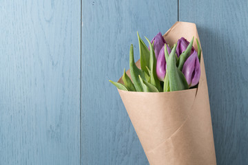 top view of purple tulips on blue wood background