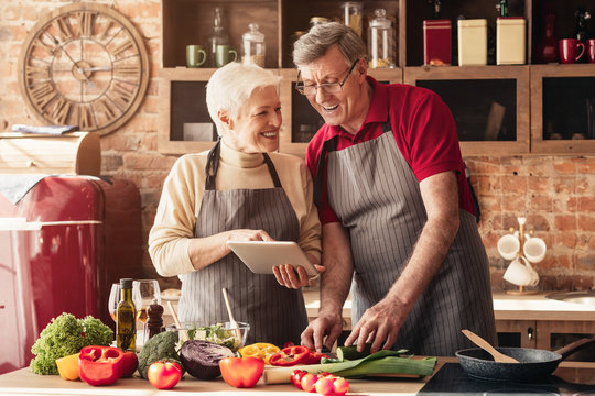 Cheerful grandparents reading exotic recipes on digital tablet