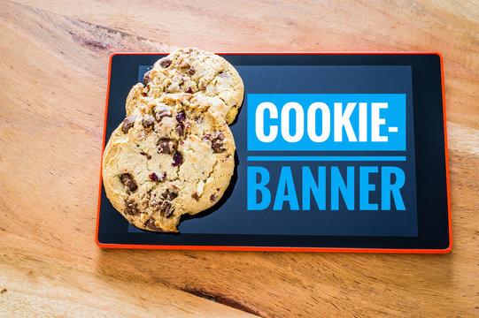 Cookies mit einem Tablet zur Verdeutlichung von Cookie Bannern für Websites mit Cookie-Banner