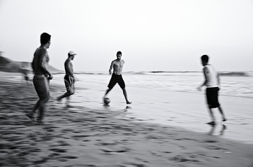 Male Friends Playing Soccer On Sea Shore Against Clear Sky