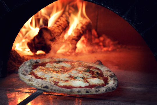 Close-Up Of Pizza Being Put In Oven