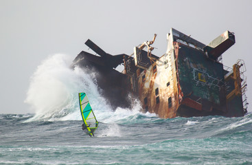 Risky windsurfing in storm on the background of the abandoned ship wrack
