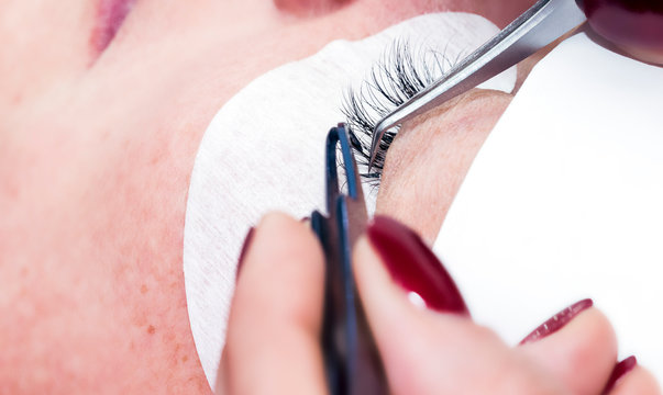 Gluing artificial eyelashes with tweezers. Cosmetic procedure. Eyelash extension. Woman eye with long eyelashes. Selective focus