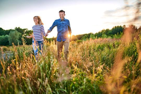 Joyful couple running through meadow on sunny summer day