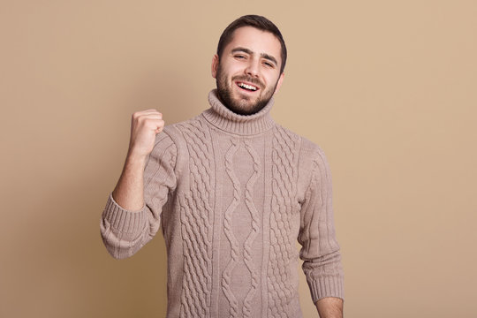 Close up portrait of young man wearing knitted sweater, posing isolated over beige background, handsome bearded guy clenching fist, screaming something happily, looking at camera., celebrating succses