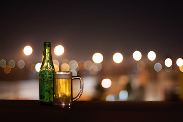 Foto auf AluDibond Alkohol An empty bottle of beer and a glass of beer on a night city lights background