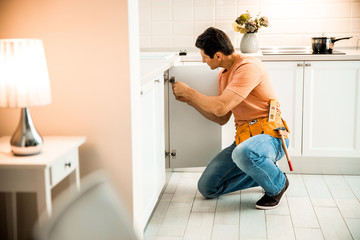 Mature man wearing belt and repairing furniture on the kitchen