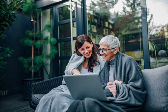 Happy beautiful older mother and adult daughter using laptop while sitting on wooden terrace, portrait.