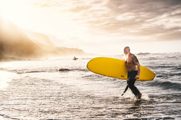 Happy fit senior surfing on sunset time - Sporty mature man having fun training with surfboard in ocean - Elderly healthy people lifestyle and extreme sport concept